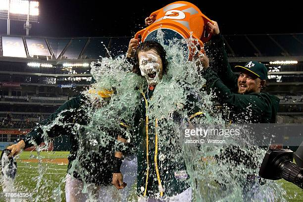 Josh Reddick of the Oakland Athletics has Gatorade poured on him by Billy Butler and Stephen Vogt after hitting a walk off RBI against the Texas...