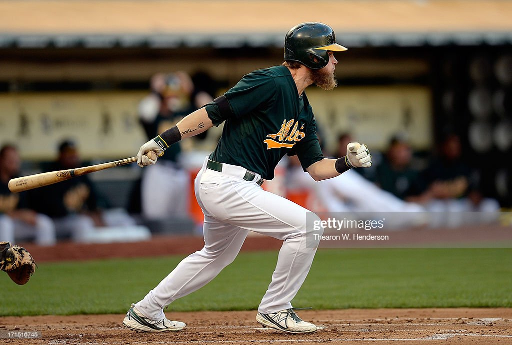 Josh Reddick #16 of the Oakland Athletics hits an RBI double scoring Brandon Moss #37 in the second inning againts the Cincinnati Reds at O.co Coliseum on June 25, 2013 in Oakland, California.