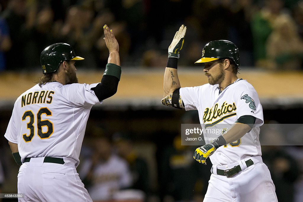 <a gi-track='captionPersonalityLinkClicked' href=/galleries/search?phrase=Josh+Reddick&family=editorial&specificpeople=5746348 ng-click='$event.stopPropagation()'>Josh Reddick</a> #16 of the Oakland Athletics is congratulated by <a gi-track='captionPersonalityLinkClicked' href=/galleries/search?phrase=Derek+Norris&family=editorial&specificpeople=6795804 ng-click='$event.stopPropagation()'>Derek Norris</a> #36 after hitting a two run home run off of Gonzalez Germen (not pictured) of the New York Mets during the eighth inning of an interleague game at O.co Coliseum on August 19, 2014 in Oakland, California. The Oakland Athletics defeated the New York Mets 6-2.