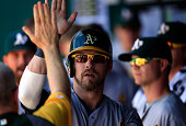 Josh Reddick of the Oakland Athletics is congratulated by teammates in the dugout after scoring during the 5th inning of the game against the Kansas...