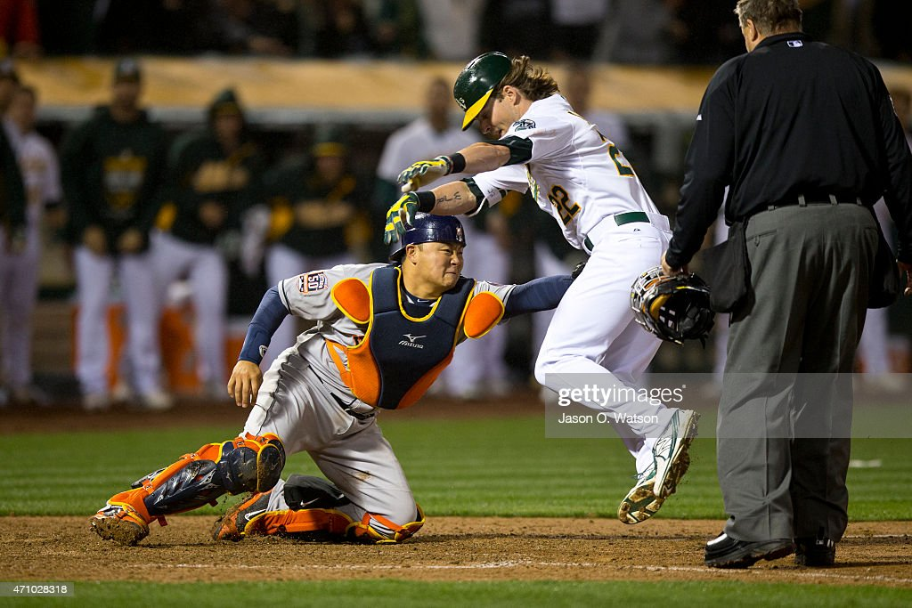<a gi-track='captionPersonalityLinkClicked' href=/galleries/search?phrase=Josh+Reddick&family=editorial&specificpeople=5746348 ng-click='$event.stopPropagation()'>Josh Reddick</a> #22 of the Oakland Athletics is tagged out at home plate by <a gi-track='captionPersonalityLinkClicked' href=/galleries/search?phrase=Hank+Conger&family=editorial&specificpeople=713039 ng-click='$event.stopPropagation()'>Hank Conger</a> #16 of the Houston Astros during the tenth inning at O.co Coliseum on April 24, 2015 in Oakland, California.