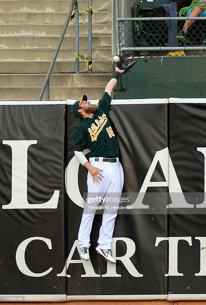 <a gi-track='captionPersonalityLinkClicked' href=/galleries/search?phrase=Josh+Reddick&family=editorial&specificpeople=5746348 ng-click='$event.stopPropagation()'>Josh Reddick</a> #16 of the Oakland Athletics leaps but is unable to make the catch of this ball that goes for a solo home run off the bat of Luis Valbuena #24 of the Chicago Cubs in the third inning at O.co Coliseum on July 3, 2013 in Oakland, California.