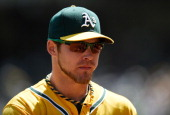 Josh Reddick of the Oakland Athletics looks on from the dugout against the Texas Rangers at Oco Coliseum on April 23 2014 in Oakland California