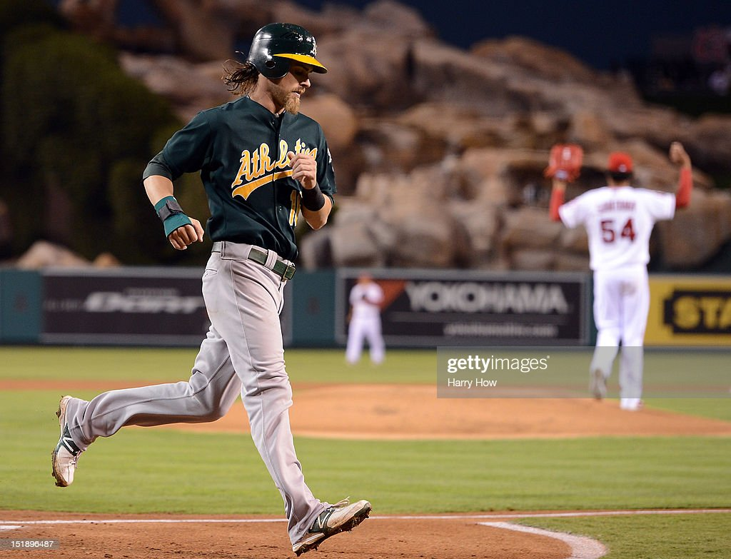 <a gi-track='captionPersonalityLinkClicked' href=/galleries/search?phrase=Josh+Reddick&family=editorial&specificpeople=5746348 ng-click='$event.stopPropagation()'>Josh Reddick</a> #16 of the Oakland Athletics scores a run off of a fielding error for a 1-0 lead in front of <a gi-track='captionPersonalityLinkClicked' href=/galleries/search?phrase=Ervin+Santana&family=editorial&specificpeople=243096 ng-click='$event.stopPropagation()'>Ervin Santana</a> #54 of the Los Angeles Angels during the first inning at Angel Stadium of Anaheim on September 12, 2012 in Anaheim, California.