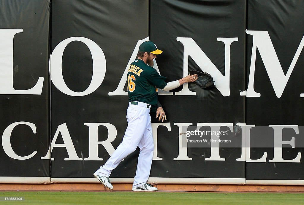 Josh Reddick #16 of the Oakland Athletics shows his frustation by slamming his glove up against the wall after he was unable to take a home run away from Luis Valbuena #24 of the Chicago Cubs in the third inning at O.co Coliseum on July 3, 2013 in Oakland, California.