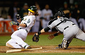 Josh Reddick of the Oakland Athletics slides safely past Geovany Soto of the Chicago White Sox to score on a hit by Billy Butler in the sixth inning...