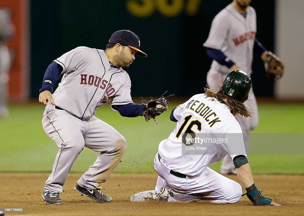 Josh Reddick #16 of the Oakland Athletics slides safely past the tag of Jose Altuve #27 of the Houston Astros to steal second base in the fourth inning at O.co Coliseum on April 16, 2013 in Oakland, California.