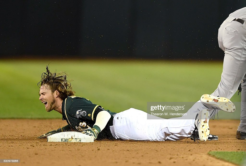 Josh Reddick #22 of the Oakland Athletics steals second base but reacts in pain after he was kicked in the head by a leaping Starlin Castro #14 of the New York Yankees in the bottom of the seventh inning at O.co Coliseum on May 19, 2016 in Oakland, California.