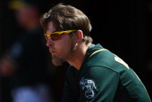 Josh Reddick of the Oakland Athletics wearing Oakley Sunglasses looks on from the dugout in the bottom of the ninth inning against the Detroit Tigers...