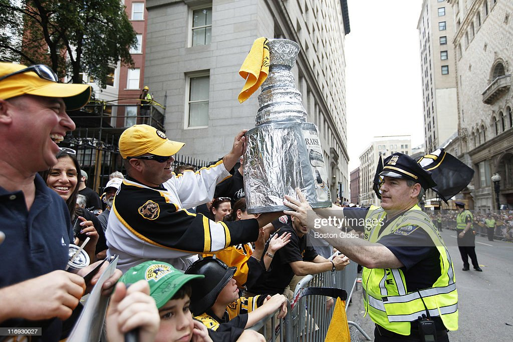 Josh Reed of Watertown lends his homemade Stanley Cup to a police officer before the start of the parade. The Boston Bruins championship parade makes its way along Tremont Street in Boston, MA on Saturday, June 18, 2011.