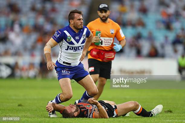 Josh Reynolds of the Bulldogs falls over an injured Robbie Farah of the Tigers during the round 10 NRL match between the Wests Tigers and the...