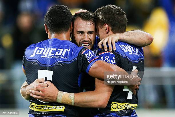 Josh Reynolds of the Bulldogs is congratulated on his try by teammates Sam Perrett and Kerrod Holland during the round seven NRL match between the...