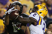 Josh Reynolds of the Texas AM Aggies catches a pass under pressure from Kevin Toliver II of the LSU Tigers at Tiger Stadium on November 28 2015 in...