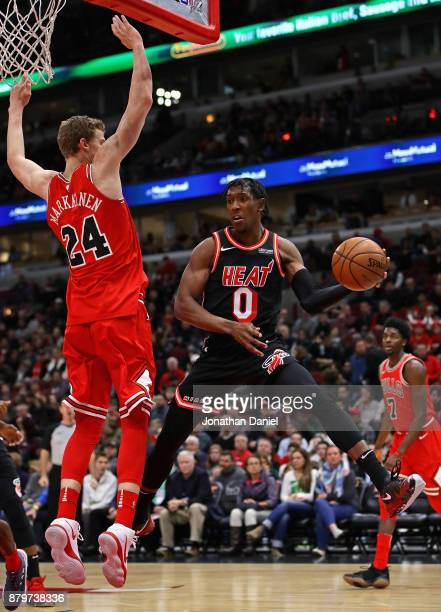 Josh Richardson of the Miami Heat leaps to pass around Lauri Markkanen of the Chicago Bulls at the United Center on November 26 2017 in Chicago...