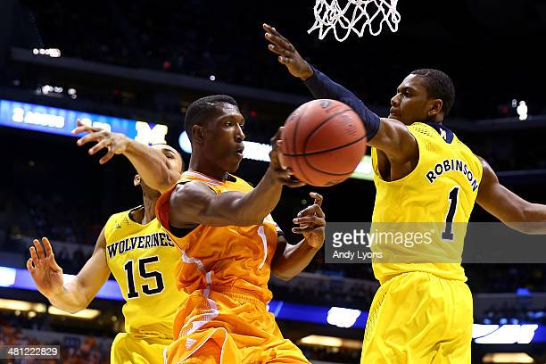 Josh Richardson of the Tennessee Volunteers passes the ball against Glenn Robinson III and Jon Horford of the Michigan Wolverines in the first half...
