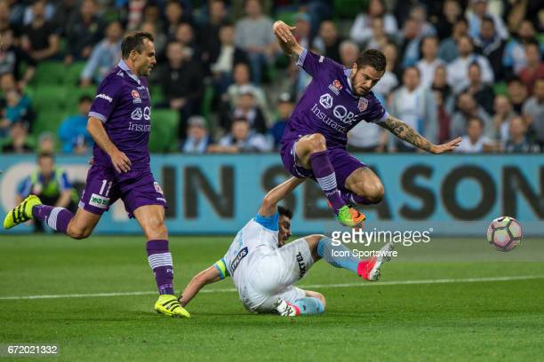 Josh Risdon of Perth Glory jumps over a tackle played by Bruno Fornaroli of Melbourne City with support from Richard Garcia of Perth Glory during the...