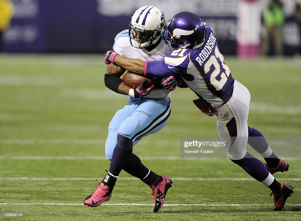 Josh Robinson #21 of the Minnesota Vikings tackles <a gi-track='captionPersonalityLinkClicked' href=/galleries/search?phrase=Javon+Ringer&family=editorial&specificpeople=2168462 ng-click='$event.stopPropagation()'>Javon Ringer</a> #21 of the Tennessee Titans during the fourth quarter of the game on October 7, 2012 at Mall of America Field at the Hubert H. Humphrey Metrodome in Minneapolis, Minnesota. The Vikings defeated the Titans 30-7.
