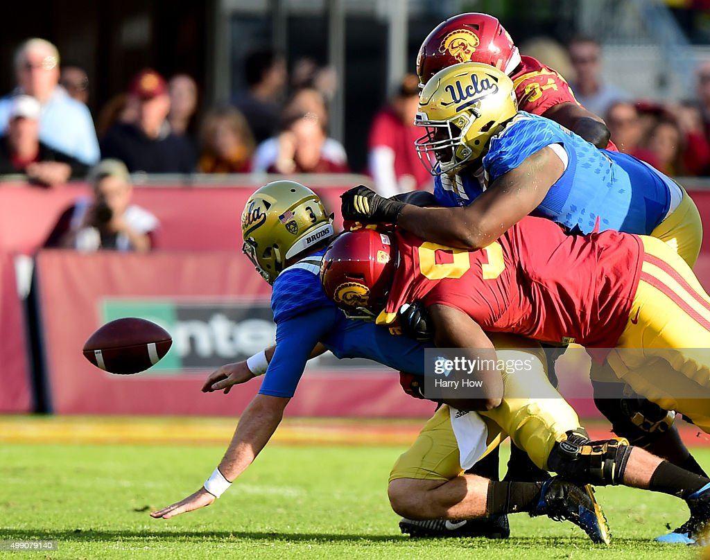 Josh Rosen #3 of the UCLA Bruins fumbles the ball as he is hit by Claude Pelon #90 of the USC Trojans during the third quarter of a 40-21 Trojan win at Los Angeles Memorial Coliseum on November 28, 2015 in Los Angeles, California.