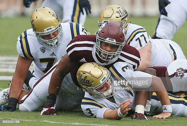 Josh Rosen of the UCLA Bruins is sacked by Myles Garrett of the Texas AM Aggies as Kolton Miller and Poasi Moala watch on September 3 2016 in College...