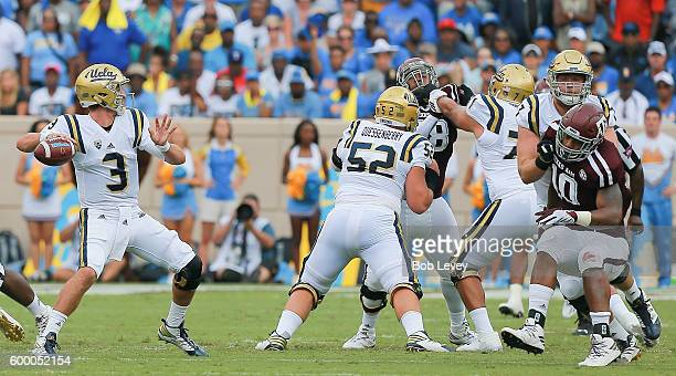 Josh Rosen of the UCLA Bruins looks for a receiver as he receives protection from Scott Quessenberry and Poasi Moala as Dyaeshon Hall of the Texas AM...