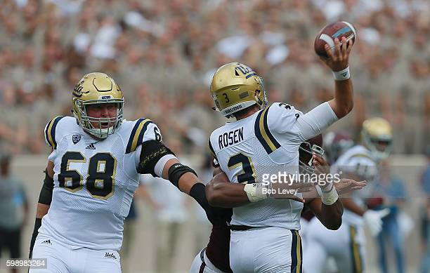 Josh Rosen of the UCLA Bruins takes a hit by Myles Garrett of the Texas AM Aggies as he releases the ball as he beat Conor McDermott of the UCLA...