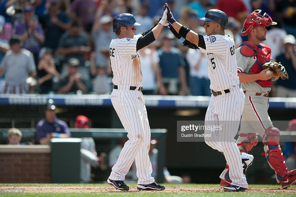 <a gi-track='captionPersonalityLinkClicked' href=/galleries/search?phrase=Josh+Rutledge&family=editorial&specificpeople=9541486 ng-click='$event.stopPropagation()'>Josh Rutledge</a> #14 and Carlos Gonzalez #5 of the Colorado Rockies celebrate a two-run eighth inning home run by Gonzalez during a game against the Philadelphia Phillies at Coors Field on June 16, 2013 in Denver, Colorado. The Rockies beat the Phillies 5-2.