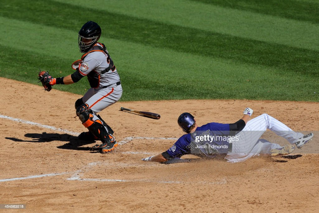 Josh Rutledge #14 of the Colorado Rockies scores ahead of the tag attempt by catcher Buster Posey #28 of the San Francisco Giants during the sixth inning at Coors Field on September 3, 2014 in Denver, Colorado.