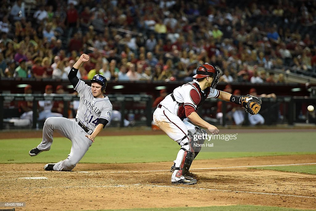 Josh Rutledge of the Colorado Rockies scores on a sacrific fly during the eighth inning as Miguel Montero of the Arizona Diamondbacks waits for the...