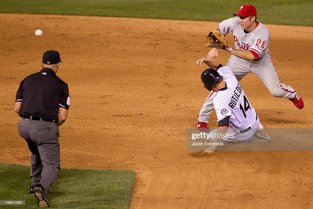 Josh Rutledge #14 of the Colorado Rockies steals second base ahead of the tag by <a gi-track='captionPersonalityLinkClicked' href=/galleries/search?phrase=Chase+Utley&family=editorial&specificpeople=161391 ng-click='$event.stopPropagation()'>Chase Utley</a> #26 of the Philadelphia Phillies under the watchful eye of second base umpire Scott Barry at Coors Field on July 13, 2012 in Denver, Colorado. The Rockies defeated the Phillies 6-2.