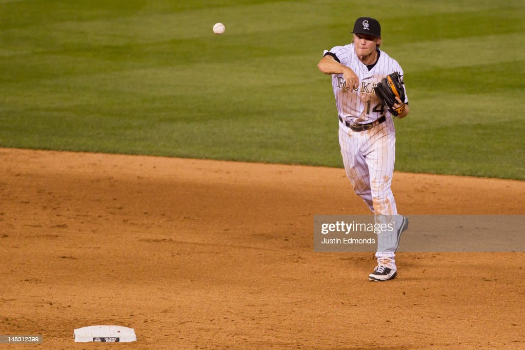 Josh Rutledge #14 of the Colorado Rockies throws to first base for the third out of the eighth inning at Coors Field on July 13, 2012 in Denver, Colorado. Rutledge made his Major League debut, going two-for-two and hitting two RBI's to help the Rockies defeat the Phillies 6-2.