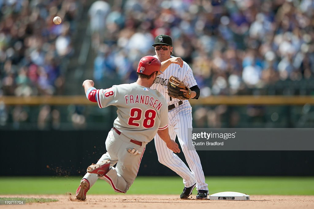 <a gi-track='captionPersonalityLinkClicked' href=/galleries/search?phrase=Josh+Rutledge&family=editorial&specificpeople=9541486 ng-click='$event.stopPropagation()'>Josh Rutledge</a> #14 of the Colorado Rockies turns a double play past a sliding <a gi-track='captionPersonalityLinkClicked' href=/galleries/search?phrase=Kevin+Frandsen&family=editorial&specificpeople=3982842 ng-click='$event.stopPropagation()'>Kevin Frandsen</a> #28 of the Philadelphia Phillies at second base at Coors Field on June 16, 2013 in Denver, Colorado. The Rockies beat the Phillies 5-2.