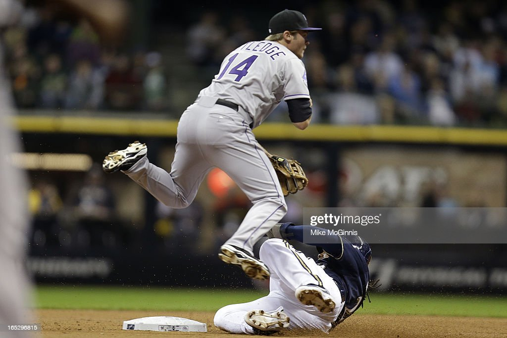 <a gi-track='captionPersonalityLinkClicked' href=/galleries/search?phrase=Josh+Rutledge&family=editorial&specificpeople=9541486 ng-click='$event.stopPropagation()'>Josh Rutledge</a> #14 of the Colorado Rockies turns the double play while <a gi-track='captionPersonalityLinkClicked' href=/galleries/search?phrase=Rickie+Weeks&family=editorial&specificpeople=550245 ng-click='$event.stopPropagation()'>Rickie Weeks</a> #23 of the Milwaukee Brewers slides into second base during the bottom of the first inning at Miller Park on April 2, 2013 in Milwaukee, Wisconsin.