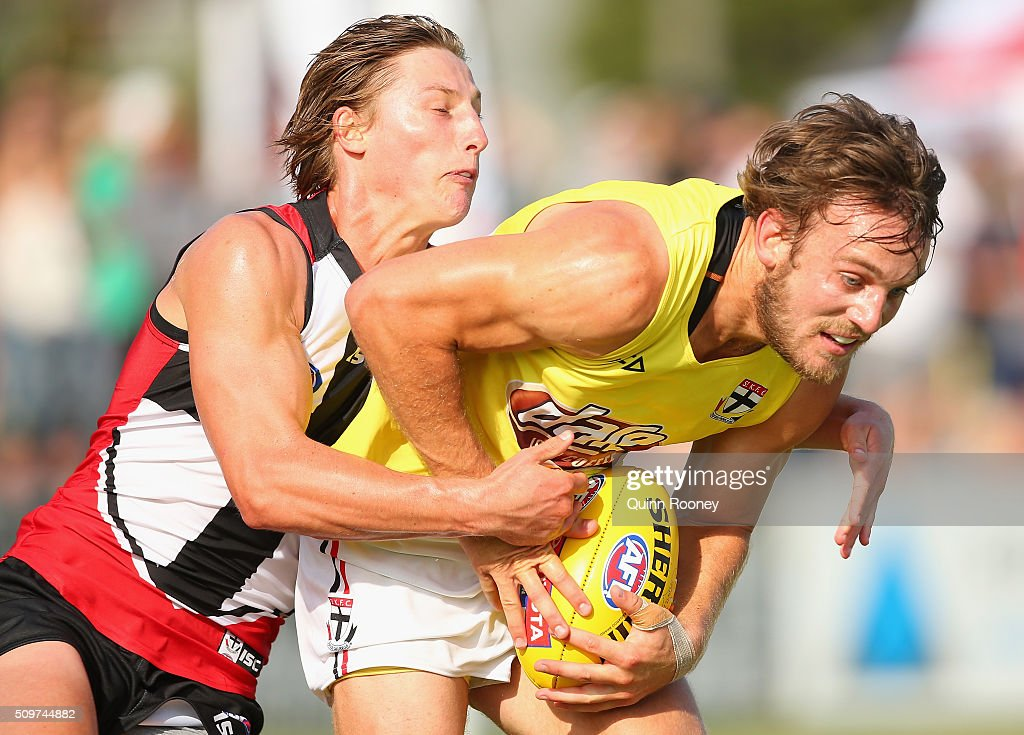 Josh Saunders of the Saints handballs whilst being tackled by Eli Templeton during the St Kilda Saints AFL Intra-Club Match at Trevor Barker Beach Oval on February 12, 2016 in Melbourne, Australia.