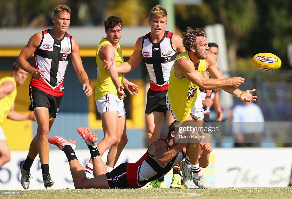 Josh Saunders of the Saints handballs whilst being tackled during the St Kilda Saints AFL Intra-Club Match at Trevor Barker Beach Oval on February 12, 2016 in Melbourne, Australia.