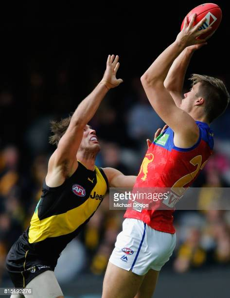 Josh Schache of the Lions marks the ball against Alex Rance of the Tigers during the round 17 AFL match between the Richmond Tigers and the Brisbane...