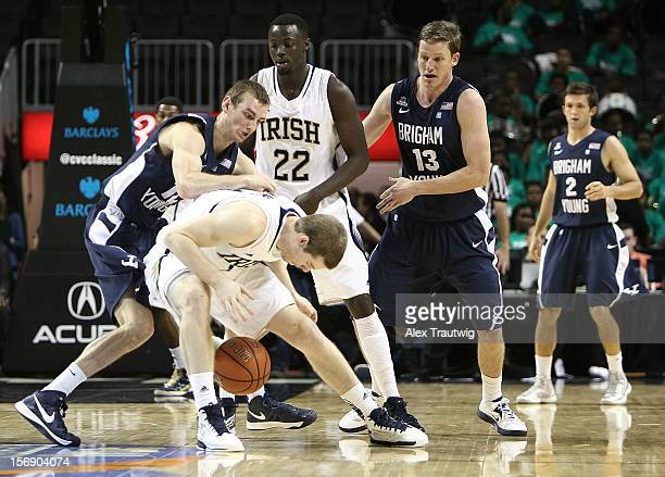 Josh Sharp of the Brigham Young Cougars and Scott Martin of the Notre Dame Fighting Irish battle for a loose ball during the consolation game of the...