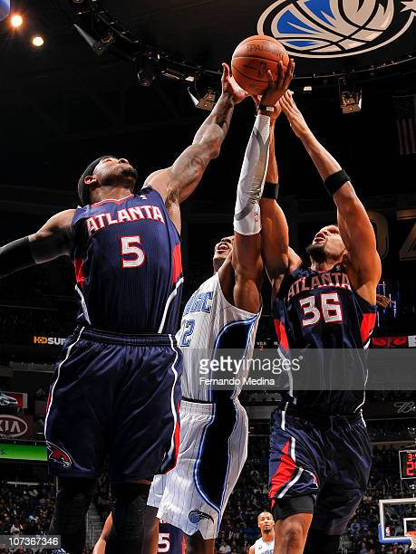 Josh Smith and Etan Thomas of the Atlanta Hawks fight for a rebound with Dwight Howard of the Orlando Magic on December 6 2010 at the Amway Center in...