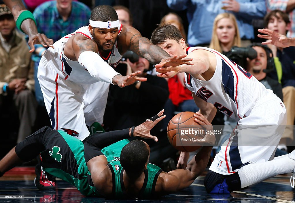 Josh Smith #5 and Kyle Korver #26 of the Atlanta Hawks reach for a loose ball recovered by Rajon Rondo #9 of the Boston Celtics at Philips Arena on January 25, 2013 in Atlanta, Georgia.