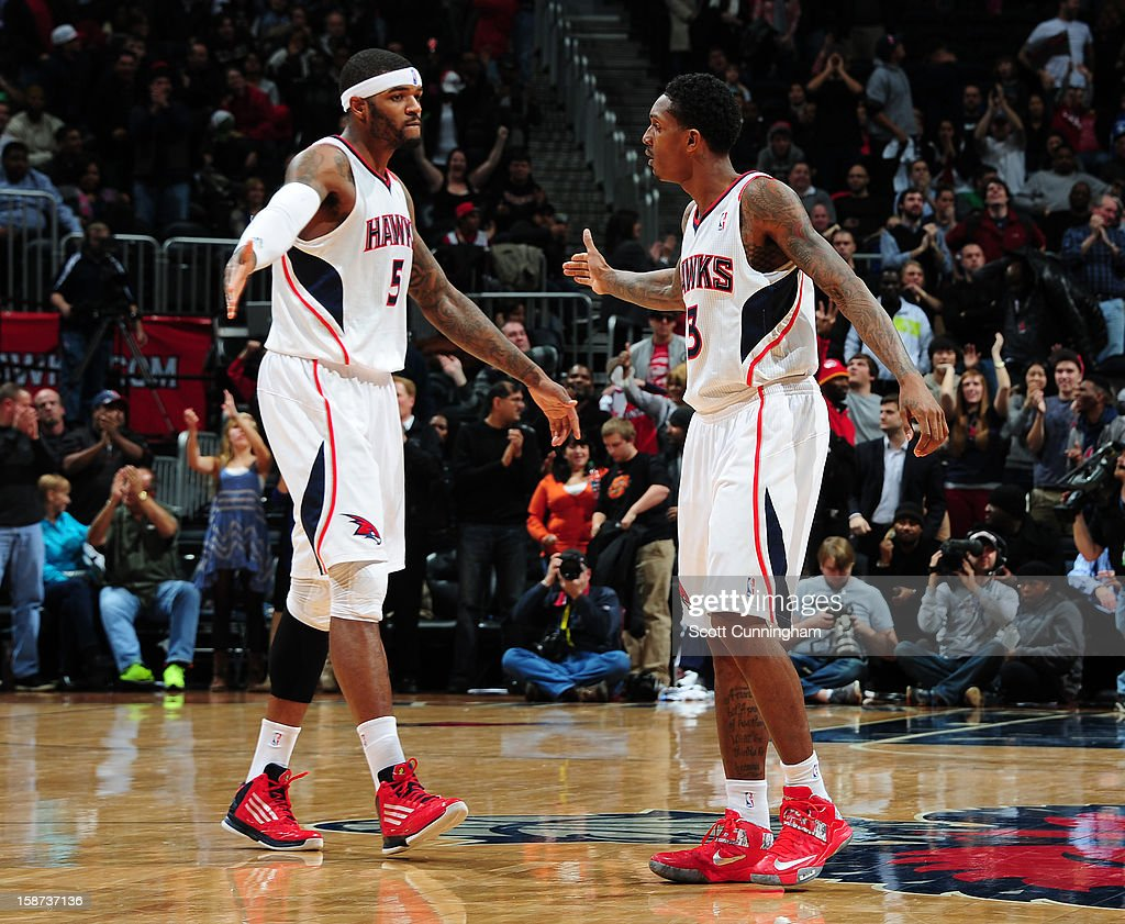 Josh Smith #5 and Louis Williams #3 of the Atlanta Hawks congratulate each other during the game against the Detroit Pistons on December 26, 2012 at Philips Arena in Atlanta, Georgia.