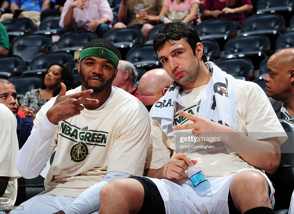 Josh Smith #5 and Zaza Pachulia #27 of the Atlanta Hawks wear 'NBA Green' shirts while sitting on the sidelines during a game against the Charlotte Bobcats on April 4, 2012 at Philips Arena in Atlanta, Georgia.
