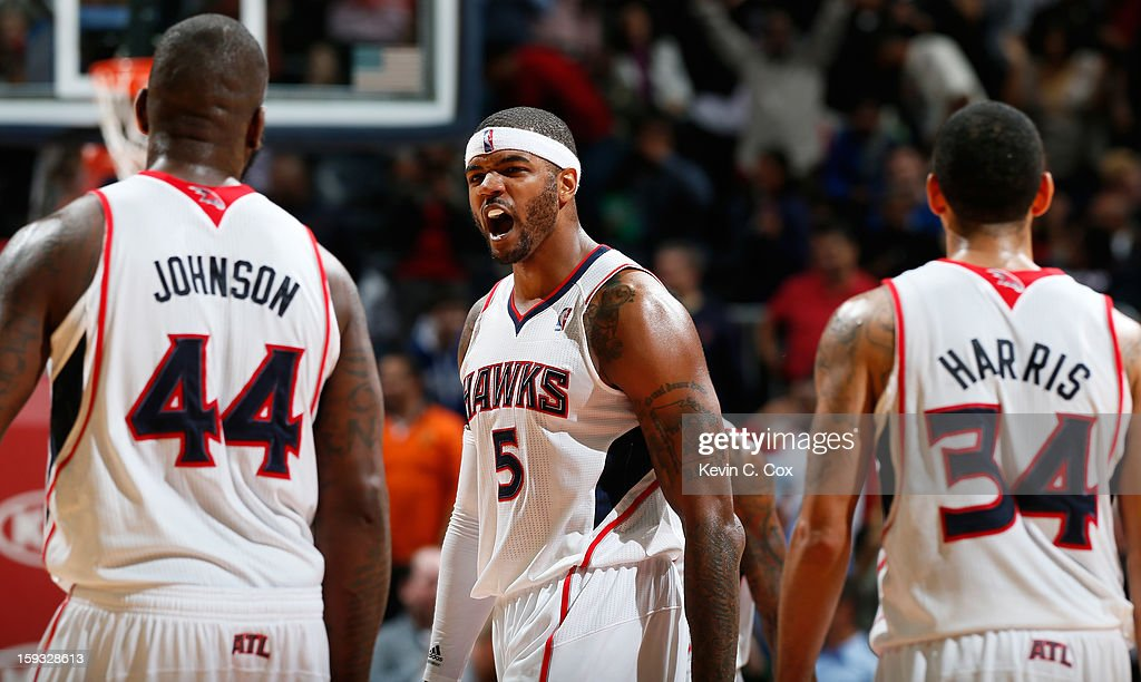 Josh Smith of the Atlanta Hawks celebrates with Ivan Johnson and Devin Harris in the final seconds against the Utah Jazz at Philips Arena on January...