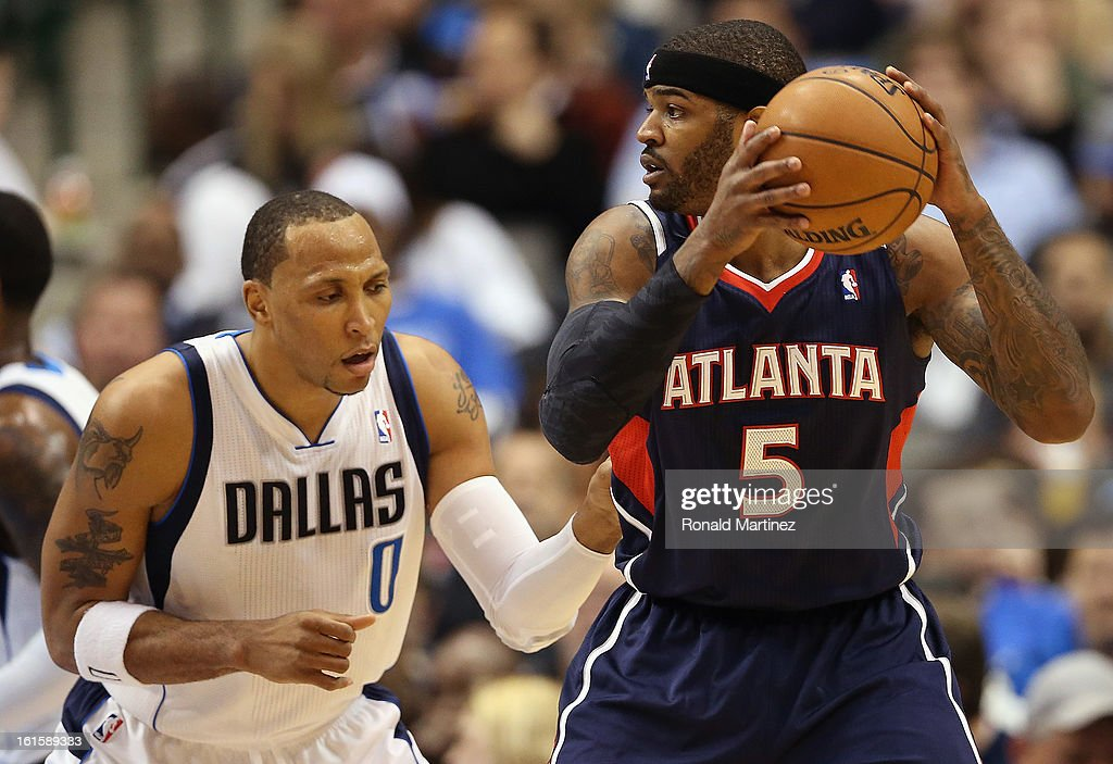 Josh Smith #5 of the Atlanta Hawks dribbles the ball against Shawn Marion #0 of the Dallas Mavericks at American Airlines Center on February 11, 2013 in Dallas, Texas.