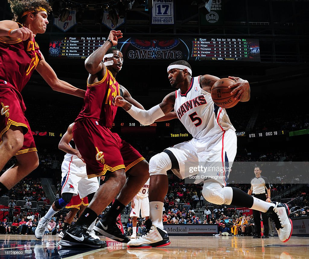 Josh Smith #5 of the Atlanta Hawks dribbles the ball against Tristan Thompson #13 amd Anderson Varejao #17 of the Cleveland Cavaliers at Philips Arena on November 30, 2012 in Atlanta, Georgia.