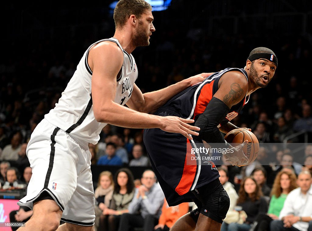 Josh Smith (R) of the Atlanta Hawks drives on Brooklyn Nets Brook Lopez March 17, 2013 at the Barclay Center in New York.