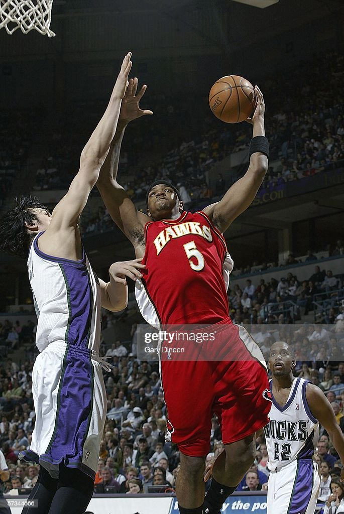 Josh Smith of the Atlanta Hawks drives to the basket against Andrew Bogut of the Milwaukee Bucks as Michael Redd of the Bucks looks on during the NBA...