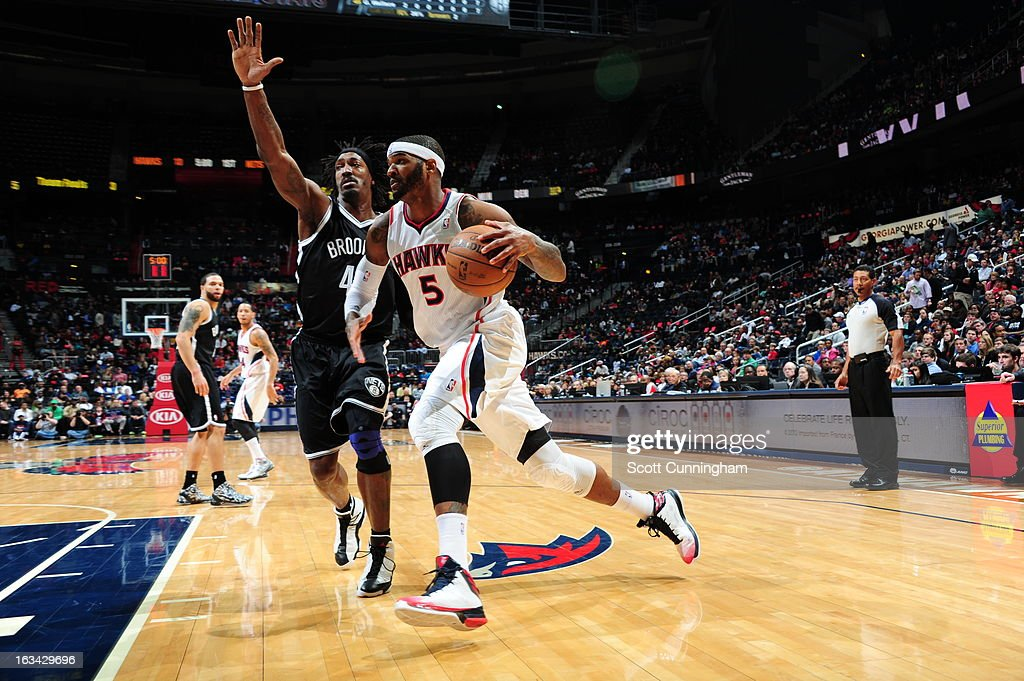 Josh Smith #5 of the Atlanta Hawks drives to the basket against Gerald Wallace #45 of the Brooklyn Nets on March 9, 2013 at Philips Arena in Atlanta, Georgia.