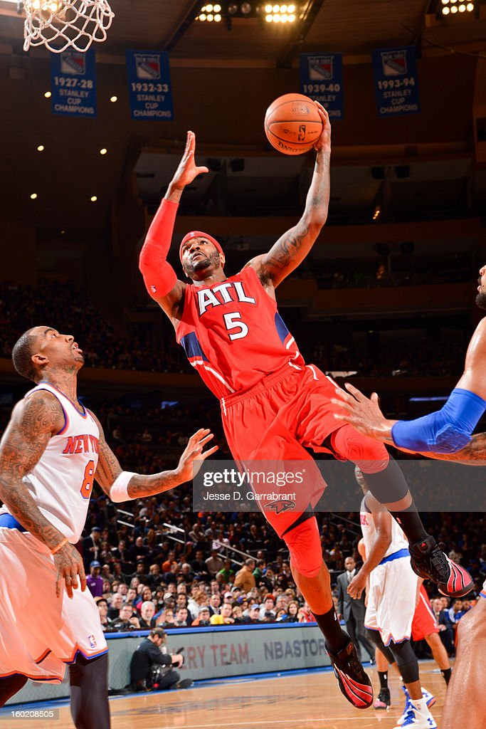 Josh Smith #5 of the Atlanta Hawks drives to the basket against J.R. Smith #8 of the New York Knicks at Madison Square Garden on January 27, 2013 in New York, New York.