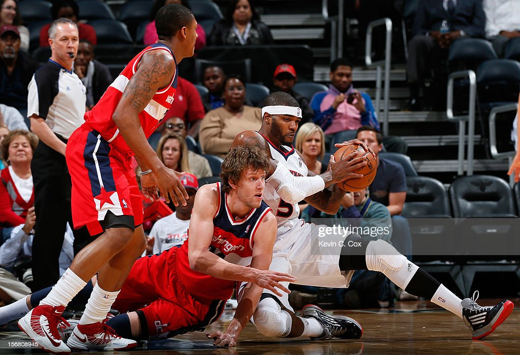 Josh Smith #5 of the Atlanta Hawks grabs a loose ball against Jan Vesely #24 and Bradley Beal #3 of the Washington Wizards at Philips Arena on November 21, 2012 in Atlanta, Georgia.