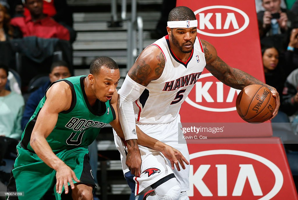 Josh Smith #5 of the Atlanta Hawks grabs a rebound against Avery Bradley #0 of the Boston Celtics at Philips Arena on January 25, 2013 in Atlanta, Georgia.