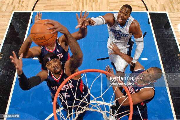 Josh Smith of the Atlanta Hawks grabs a rebound against Dwight Howard of the Orlando Magic on November 8 2010 at the Amway Center in Orlando Florida...